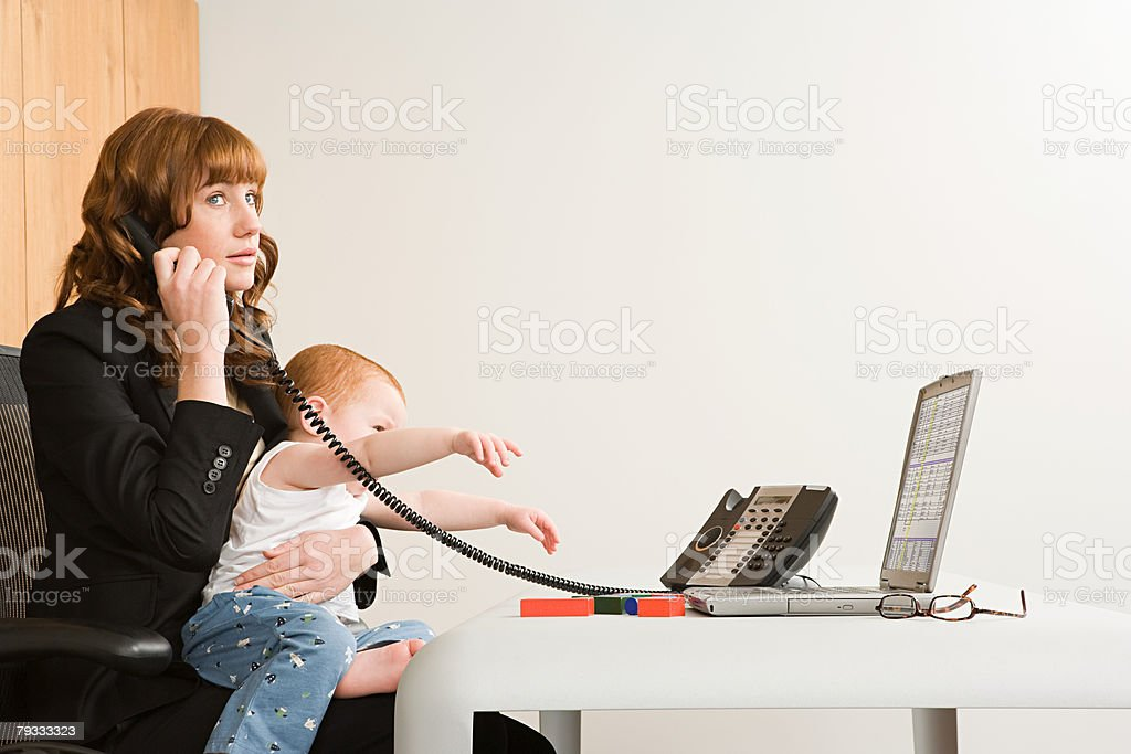 A businesswoman using telephone and holding son royalty-free stock photo