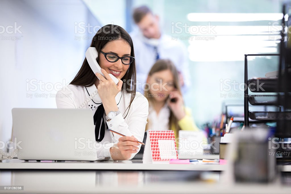 Businesswoman using telephone at desk in office stock photo