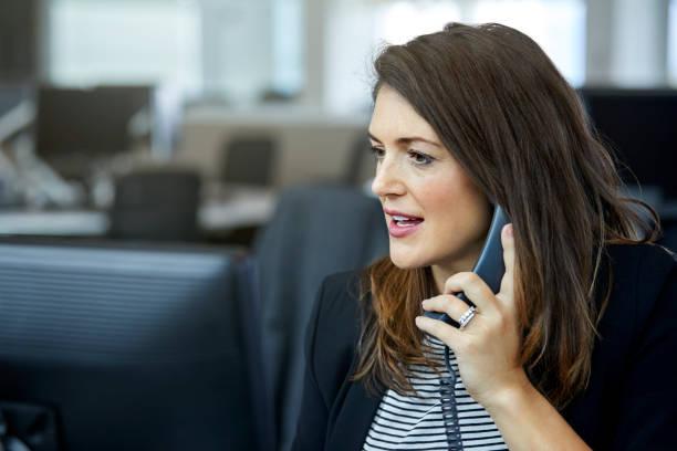 businesswoman using telephone at desk - cornetta telefono foto e immagini stock