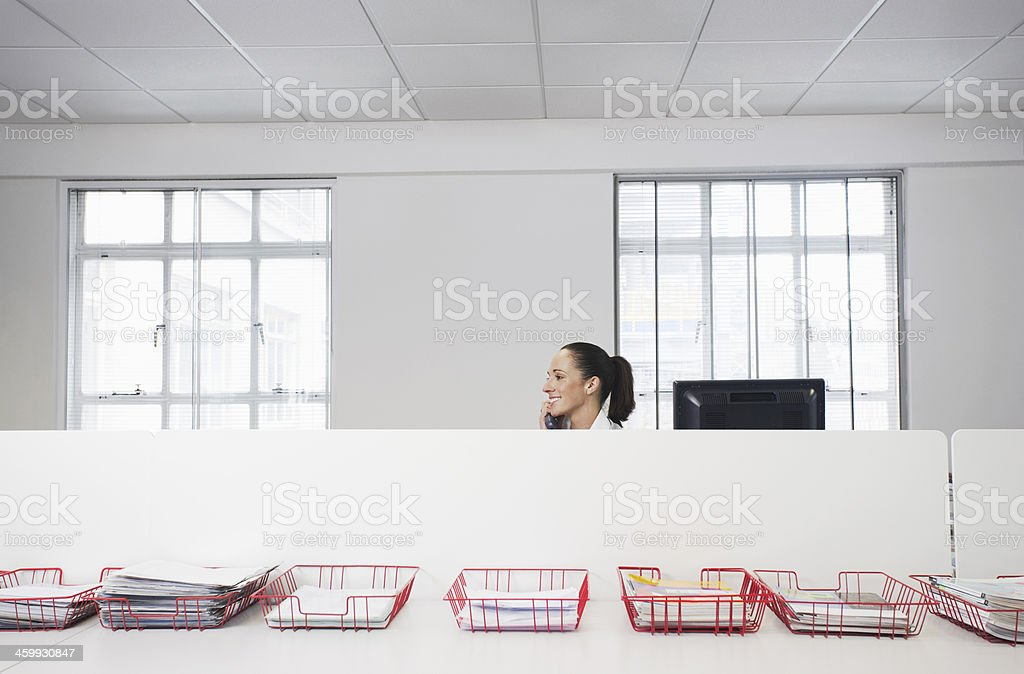 Businesswoman Using Telephone With Trays Of Documents On Table stock photo