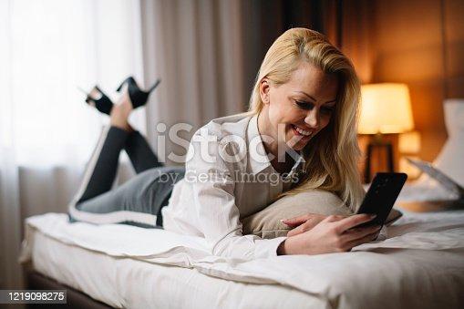 947825822 istock photo Businesswoman using the phone in hotel. 1219098275