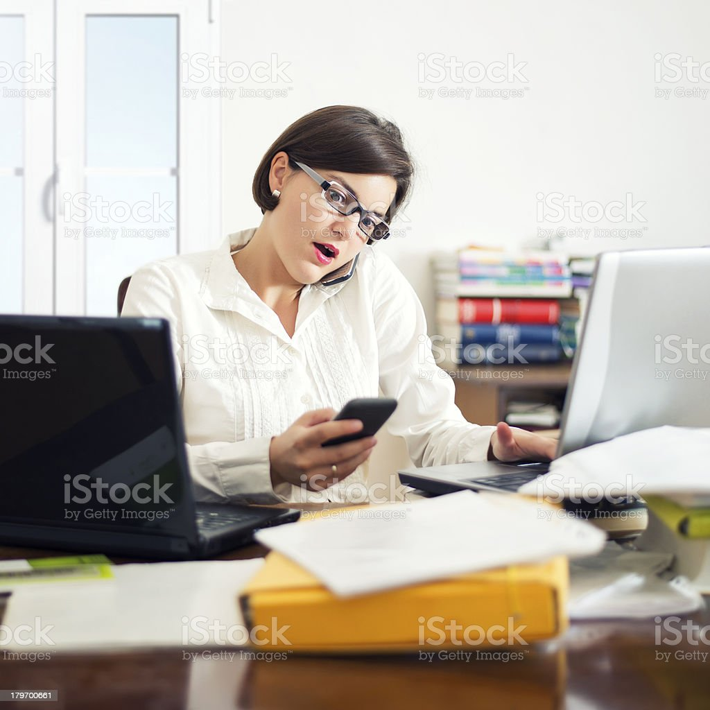 Businesswoman using two phones at desk royalty-free stock photo