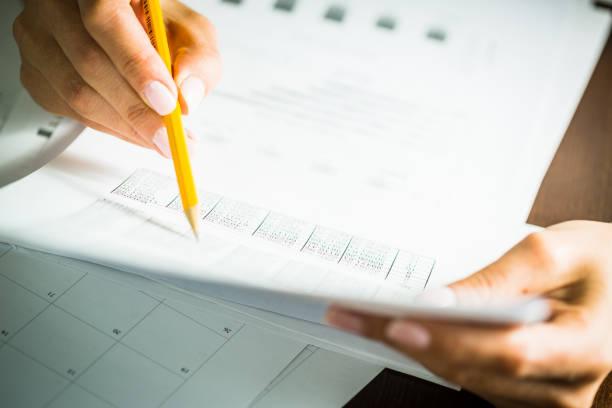 geschäftsfrau überprüfen dokument, nahaufnahme von hand mit bleistift - lesen arbeitsblätter stock-fotos und bilder