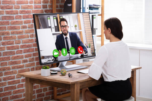 businesswoman video conferencing with businessman - virtual meeting стоковые фото и изображения