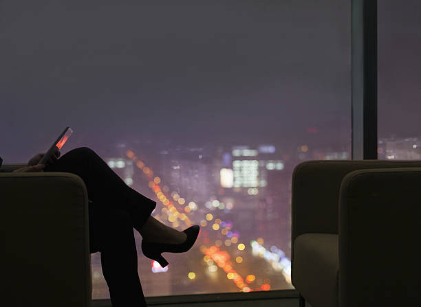 businesswoman viewing tablet computer in office at night - privacy policy stock photos and pictures