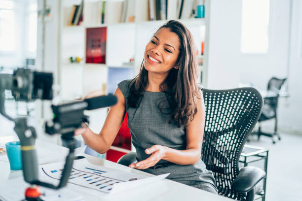 businesswoman vlogging at the office - violetastoimenova stock photos and pictures