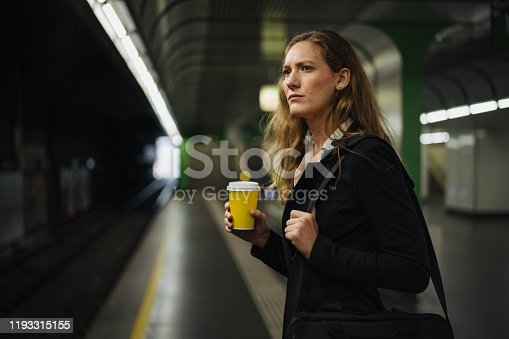 Serious businesswoman is standing at a subway station, holding coffee to go and waiting for a train.