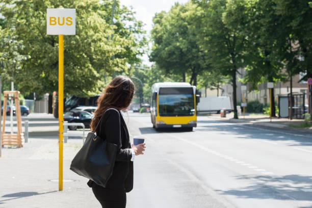 zakenvrouw wachten op bus - bushalte stockfoto's en -beelden