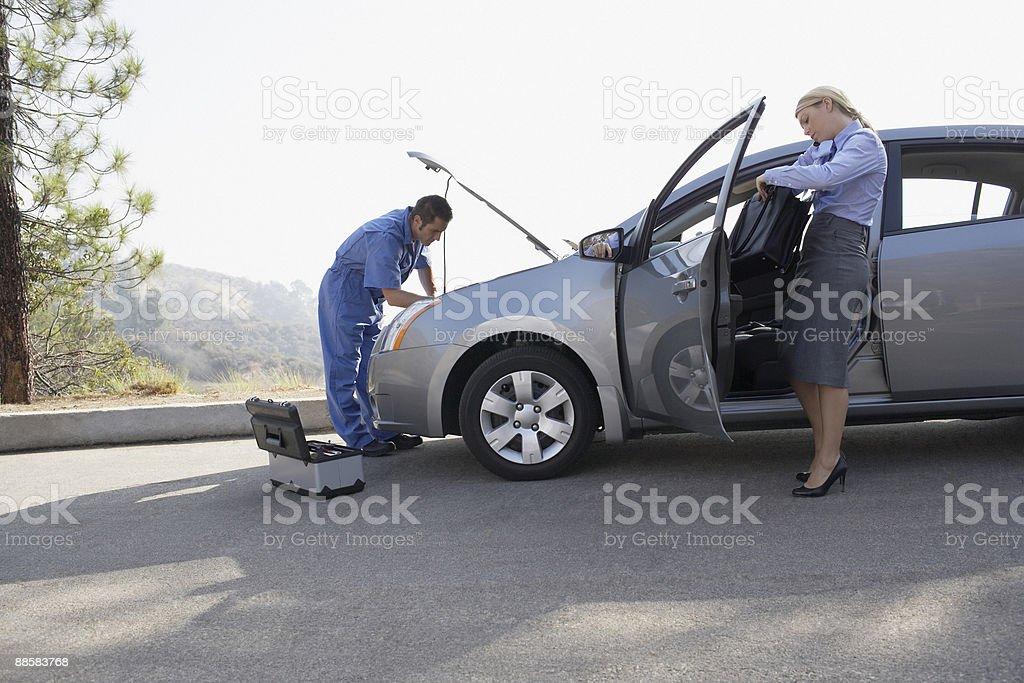 Femme d'affaires attend Mécanicien de réparer la voiture photo libre de droits