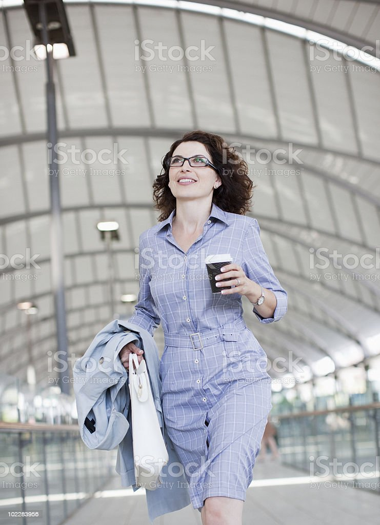 Businesswoman walking and holding coffee stock photo