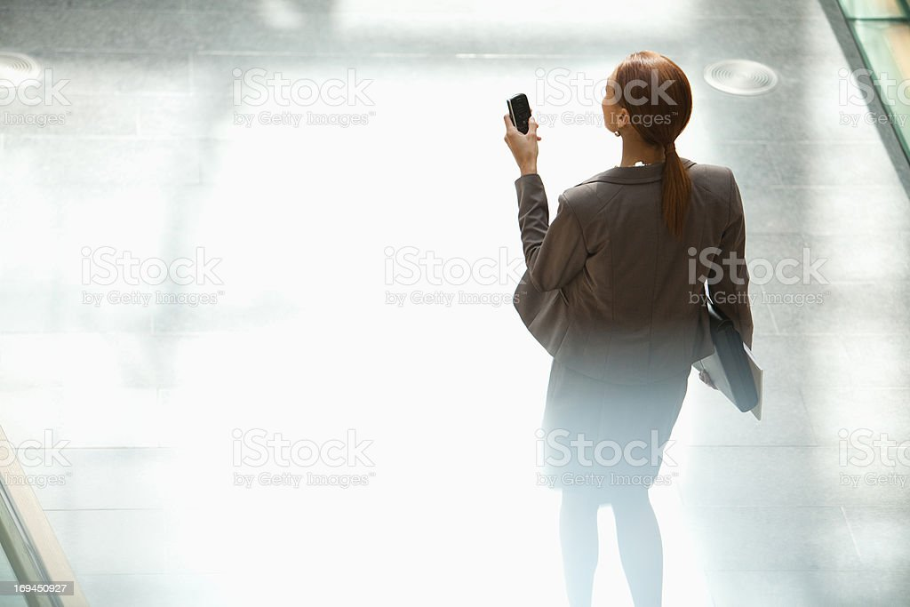 Businesswoman walking and looking down at cell phone royalty-free stock photo