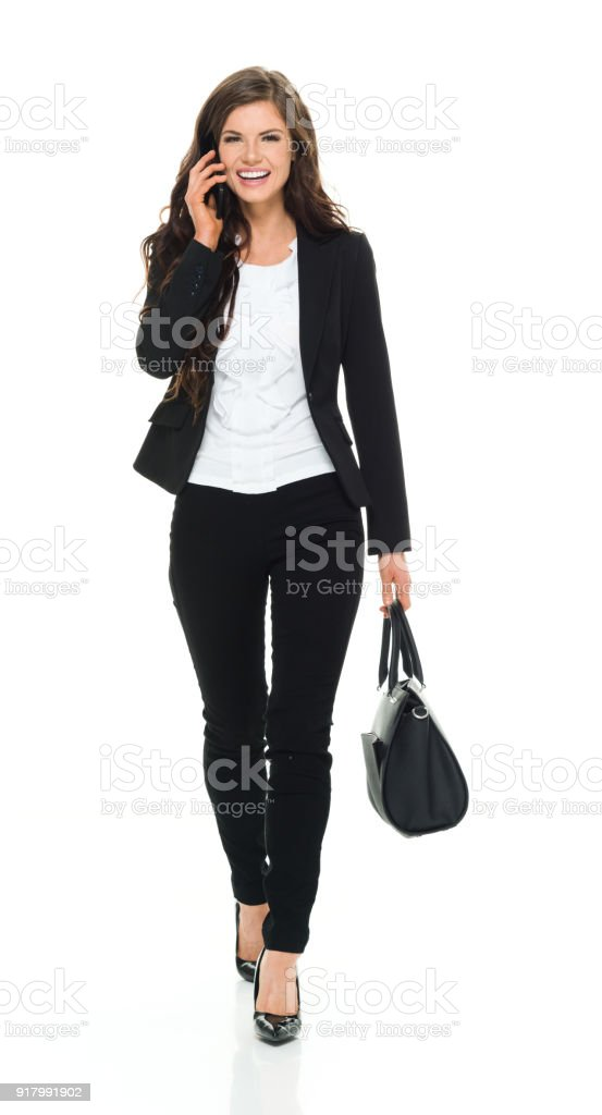 Businesswoman walking and talking on phone stock photo