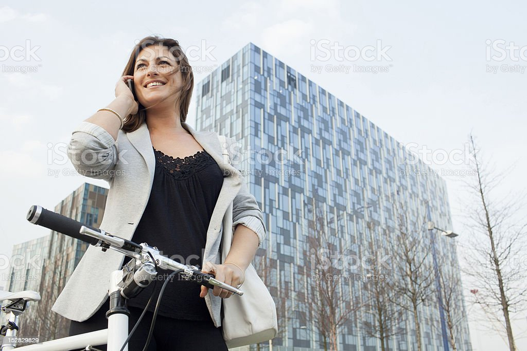 Businesswoman walking bicycle outdoors stock photo