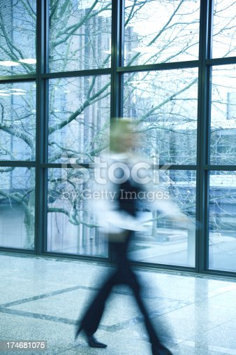 171150458 istock photo Businesswoman Walking in Corridor, Blurred Motion 174681075