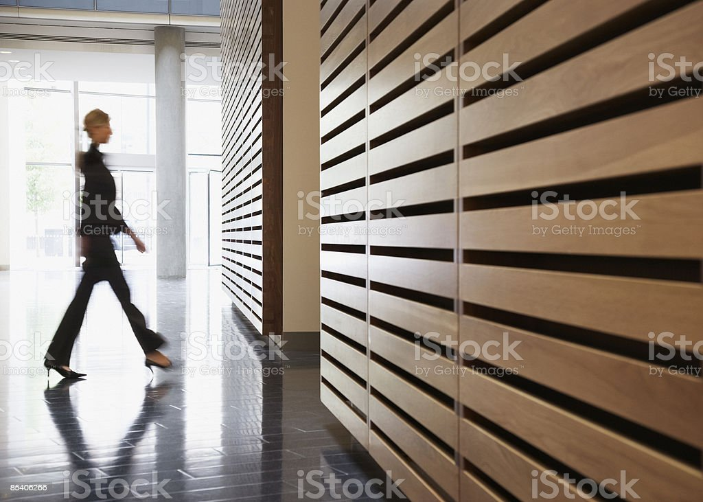 Businesswoman walking in corridor stock photo