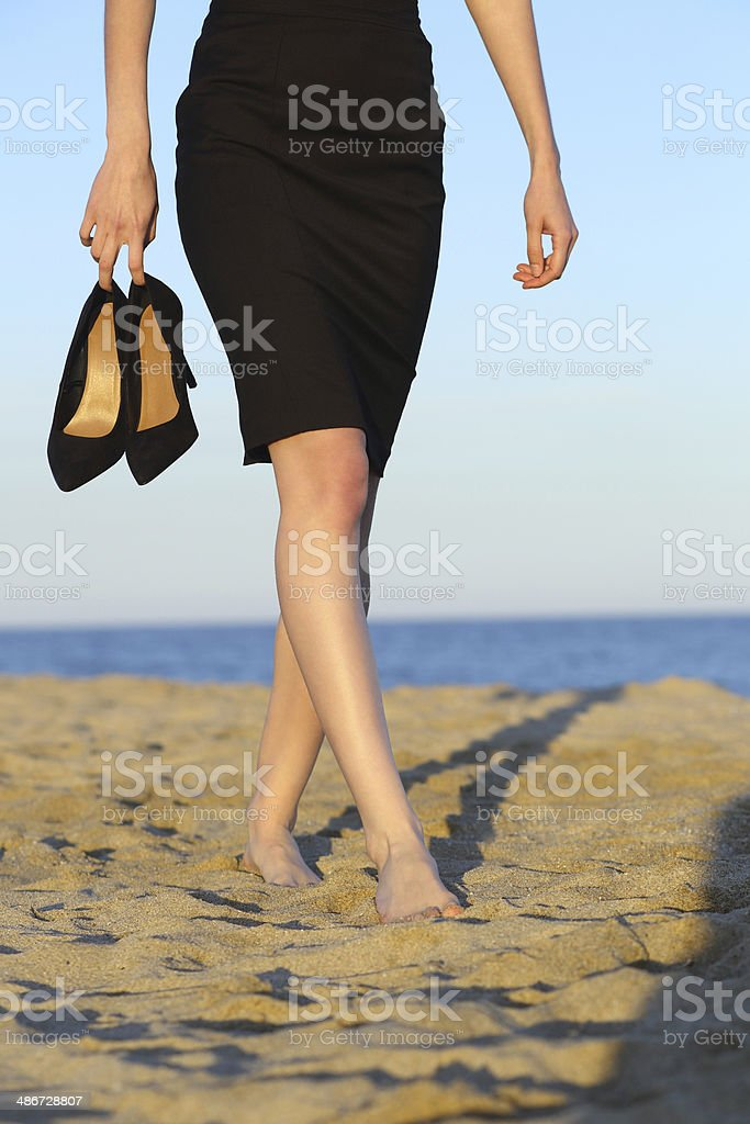 Businesswoman walking on the beach with heels on her hand stock photo