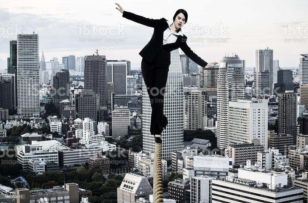 Businesswoman walking on tightrope stock photo
