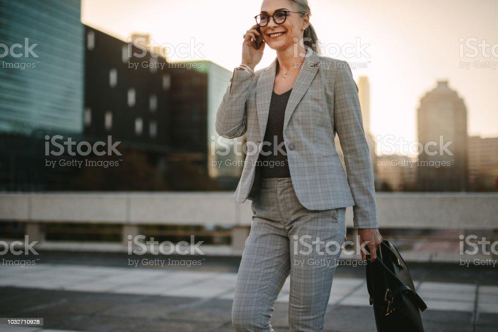 Beautiful senior woman walking outside on road talking on phone....
