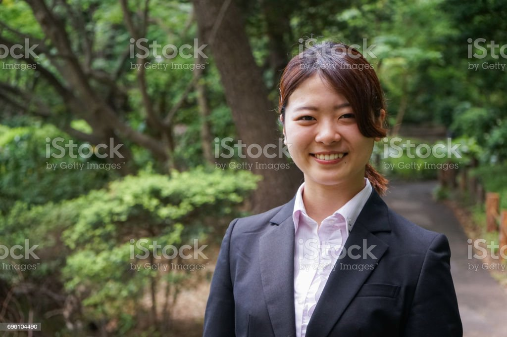 Businesswoman walking outdoors with smile stock photo