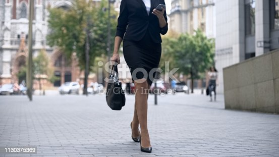 istock Businesswoman walking to work and using smartphone, busy lifestyle in big city 1130375369