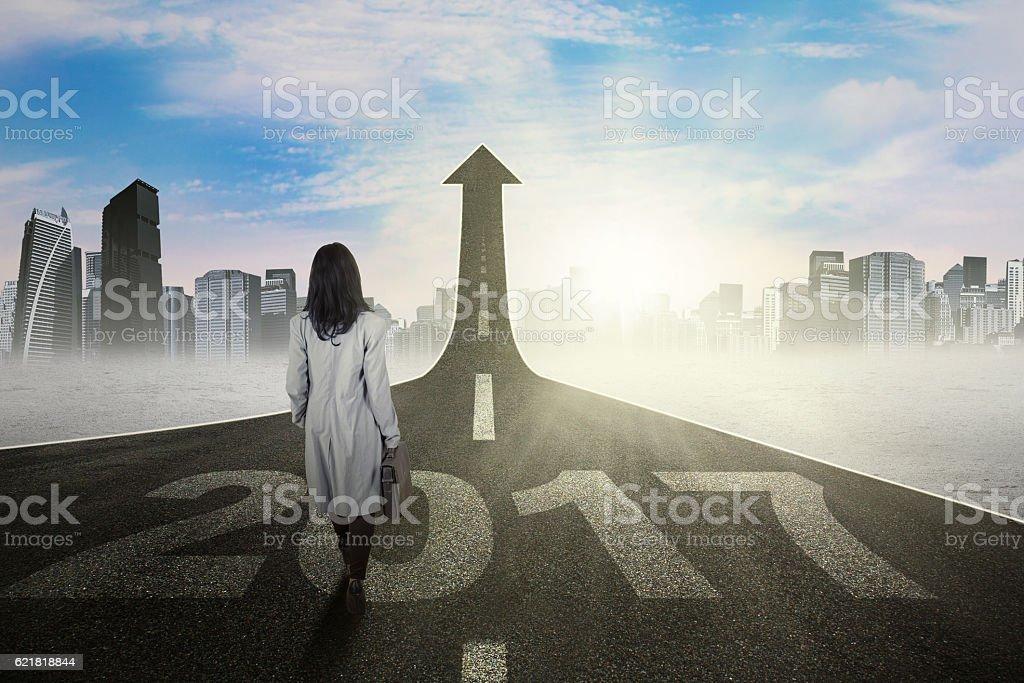 Businesswoman walking toward arrow with 2017 stock photo