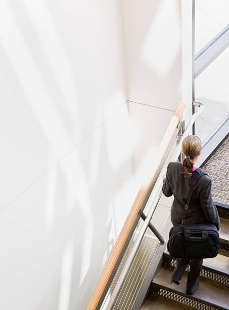 Businesswoman Walking Up Stairs stock photo