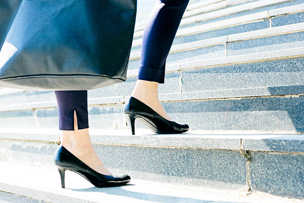 businesswoman walking up stairs to higher level - flat shoe stock photos and pictures