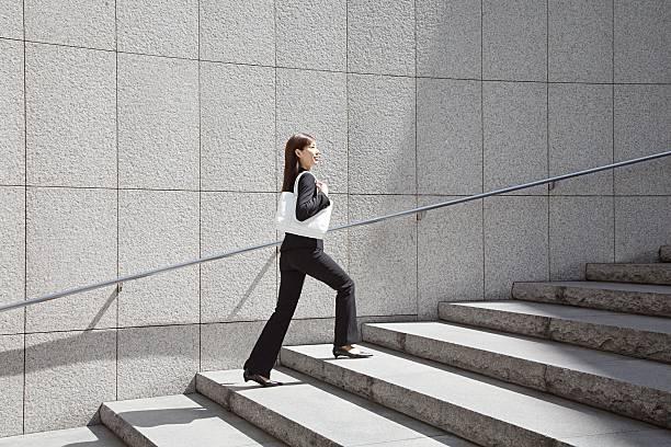 femme d'affaires marche jusqu'à quelques pas - marches marches et escaliers photos et images de collection