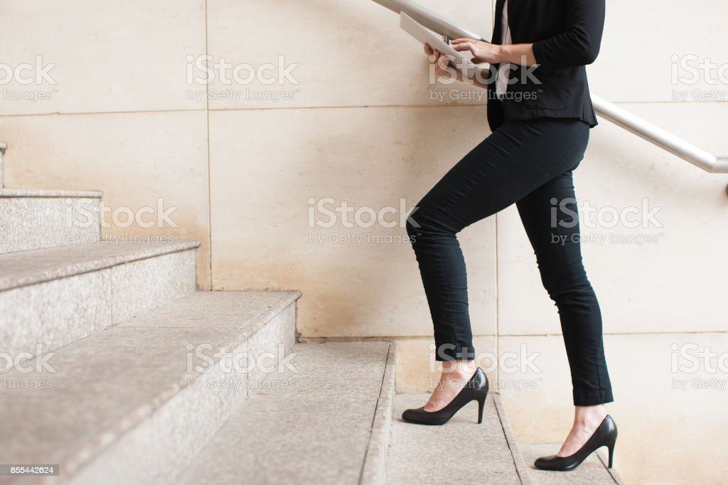 Businesswoman walking upstairs and using touchpad stock photo