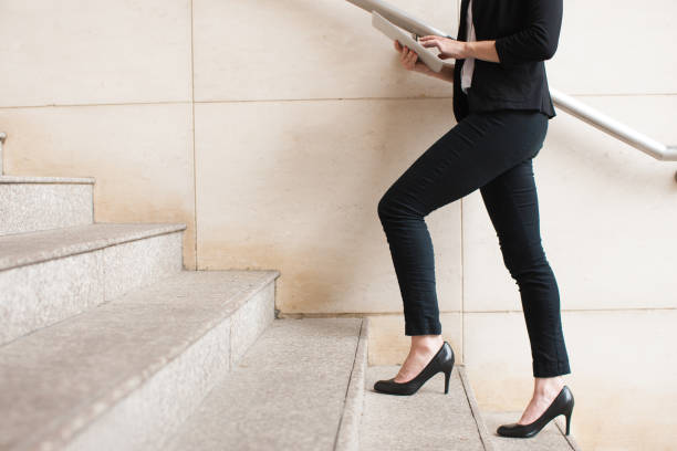 businesswoman walking upstairs and using touchpad - staircase stock photos and pictures
