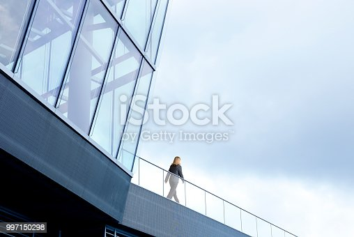 A businesswoman walks along a walkway outside of a modern office building.  The overcast sky in the background provides ample room for text and copy.