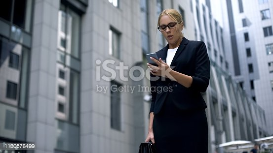 Businesswoman watching deal online via smartphone, worrying about investments