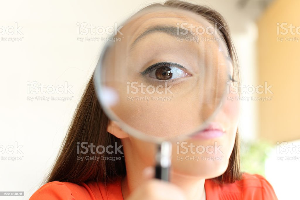 Businesswoman watching you with magnifier glass stock photo