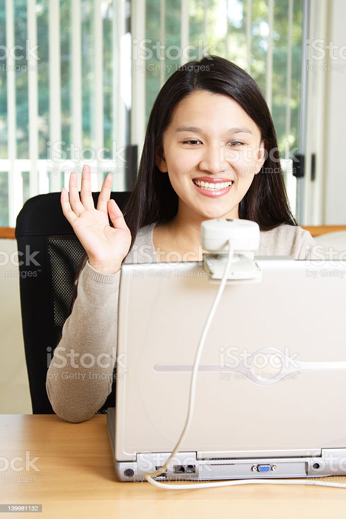 Businesswoman waves at webcam on her laptop stock photo