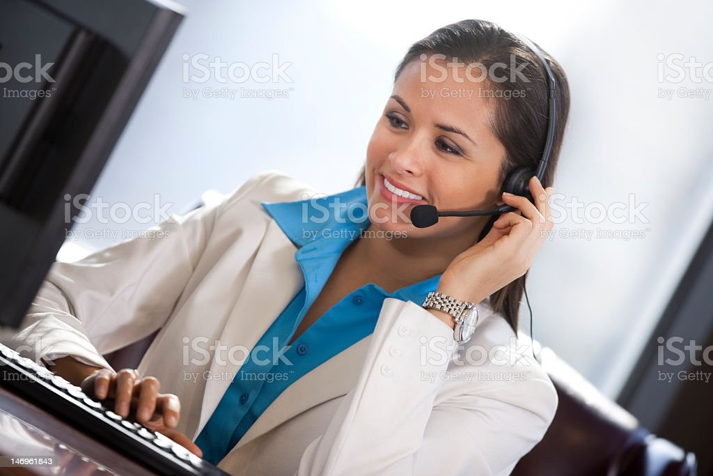 Businesswoman wearing a headset while using computer royalty-free stock photo