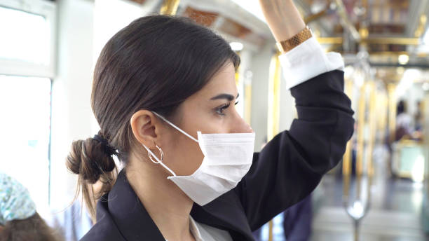 Businesswoman wearing a mask while traveling stock photo