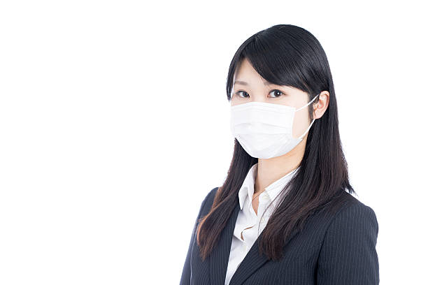 businesswoman wearing a surgical mask - マスク 日本人 ストックフォトと画像