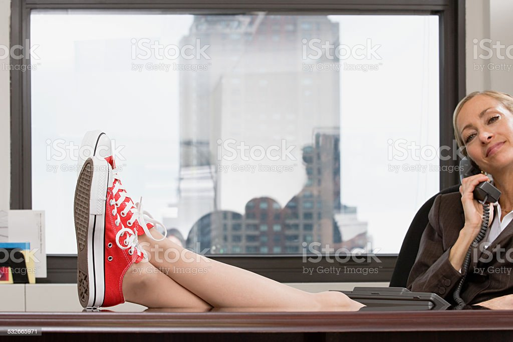 Businesswoman wearing baseball boots stock photo