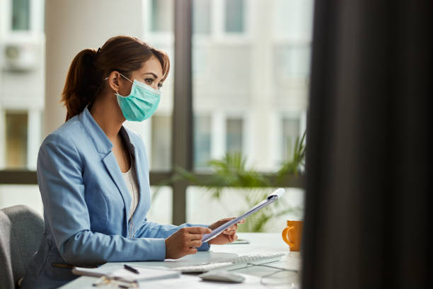 Businesswoman wearing face mask while analzying reports in the office. stock photo