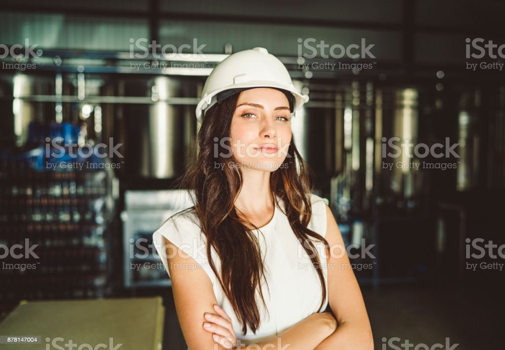 Businesswoman wearing hardhat in brewery stock photo