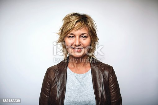 Portrait of mature businesswoman wearing leather jacket. Female is smiling. She is over white background.