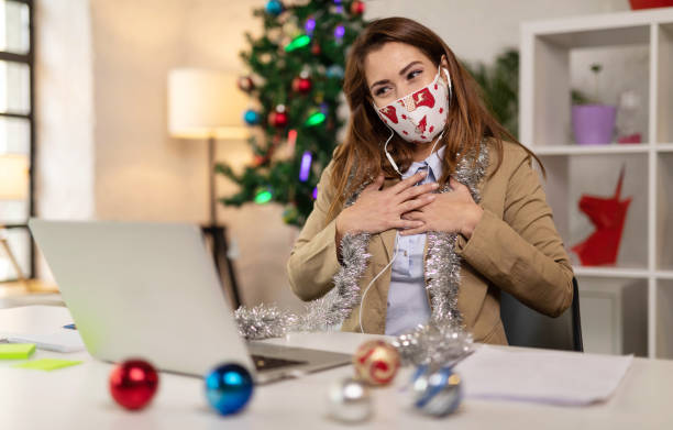 Businesswoman wearing protective face mask having a video call at home stock photo