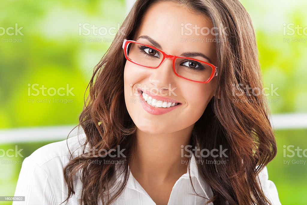 A businesswoman wearing red glasses and smiling royalty-free stock photo