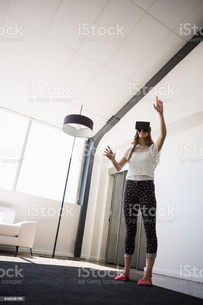 Businesswoman wearing virtual reality simulator in office stock photo