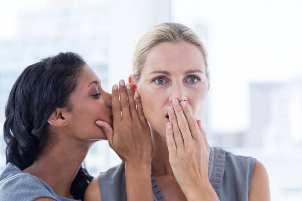 Businesswoman whispering gossip to her colleague - Photo