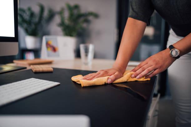 businesswoman wiping sher work desk, close-up. - cleaning zdjęcia i obrazy z banku zdjęć