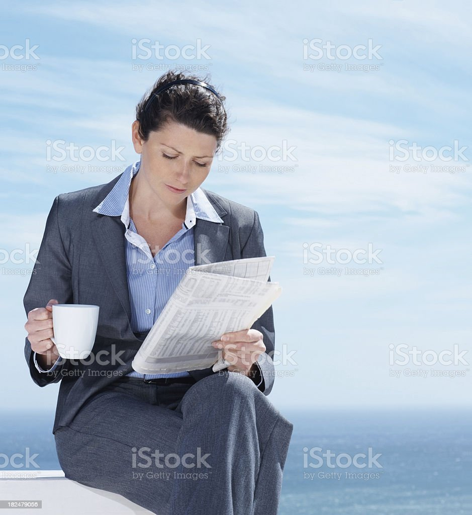 Businesswoman with a coffee and reading newspaper by sea royalty-free stock photo