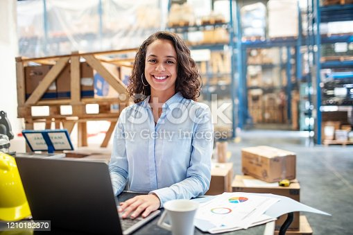 Smiling business woman working on laptop at a warehouse. Businesswoman with a laptop working at a distribution warehouse.