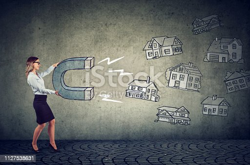 istock Businesswoman with a magnet attracting house buyers and household votes 1127538631