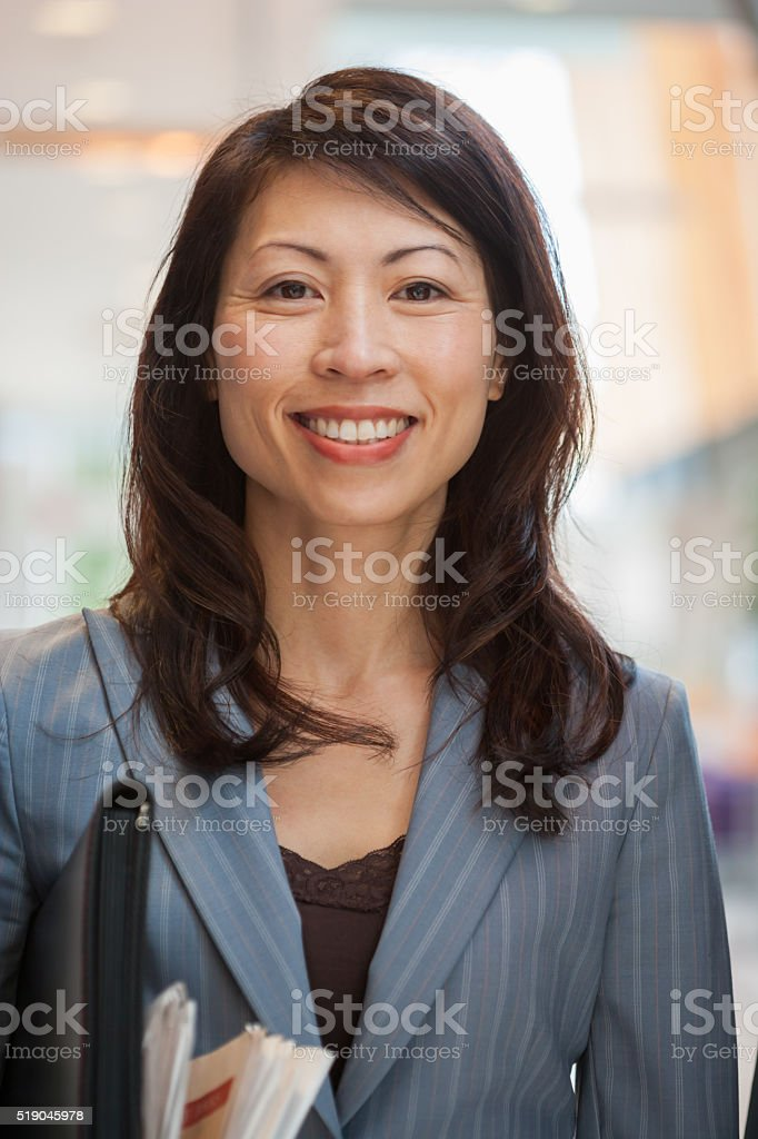Businesswoman with a newspaper and briefcase stock photo